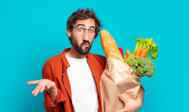 Jonge, bebaarde man voelt zich verbaasd en verward, twijfelt, weegt of kiest verschillende opties met grappige uitdrukking en houdt een zak met groenten vast
