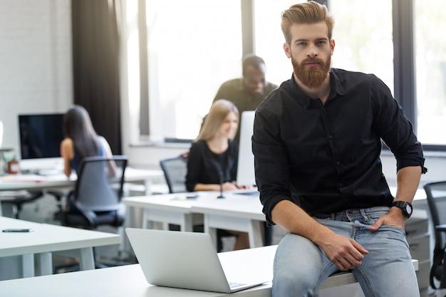 Jonge, bebaarde man zit op zijn bureau in een kantoor