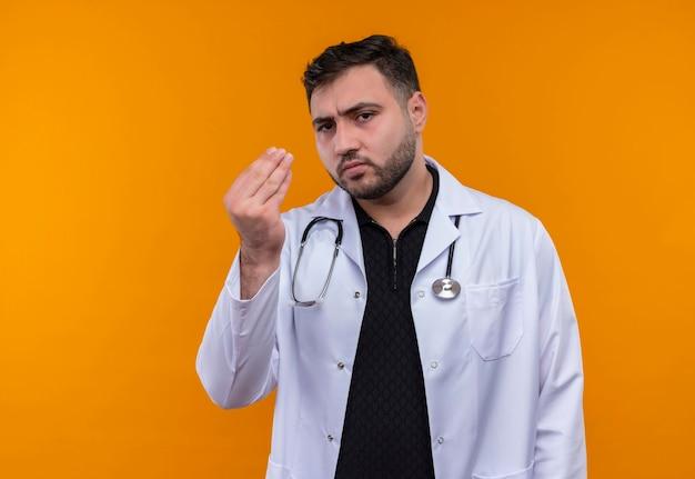 Jonge, bebaarde mannelijke arts die een witte jas met een stethoscoop draagt die ontevreden met de hand gebaren kijkt