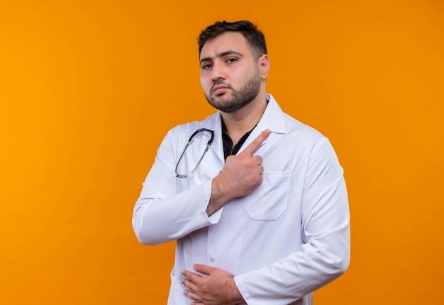 Jonge, bebaarde mannelijke arts die witte jas draagt met een stethoscoop die met wijsvinger naar de kant richt die er zelfverzekerd uitziet