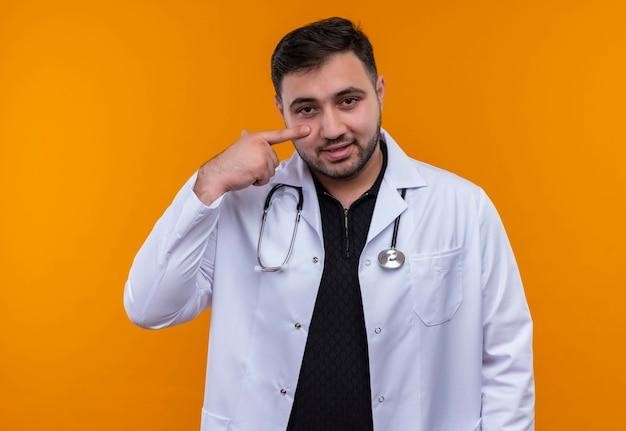 Jonge, bebaarde mannelijke arts die witte jas draagt met een stethoscoop die met wijsvinger naar zijn gezicht het glimlachen richt