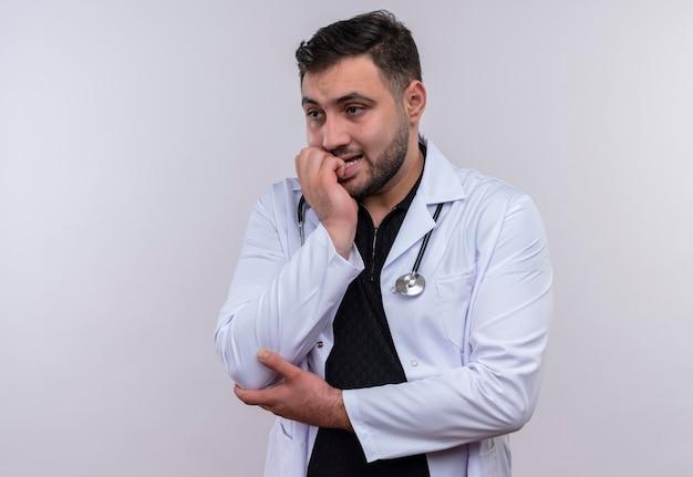 Jonge, bebaarde mannelijke arts die witte jas met een stethoscoop draagt, benadrukt en zenuwachtig zijn spijkers bijt