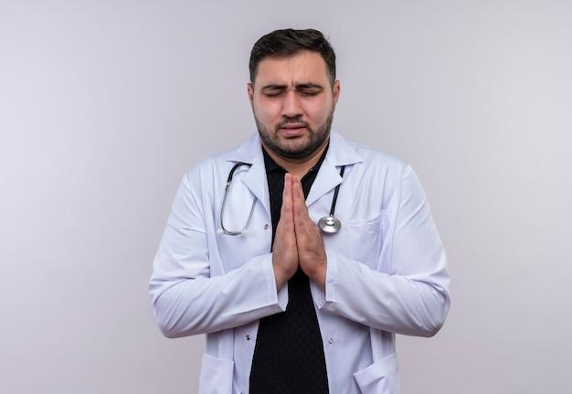 Jonge, bebaarde mannelijke arts die witte jas met een stethoscoop draagt die de wapens bij elkaar houdt, bidt en bedelt met hoop uitdrukking