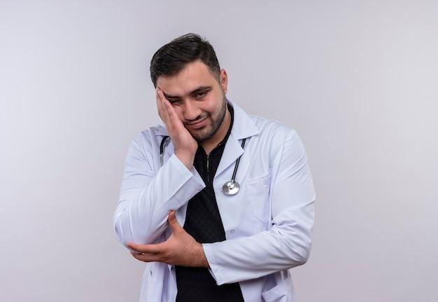 Jonge, bebaarde mannelijke arts die witte jas met een stethoscoop draagt die er moe en verveeld uitziet, zijn hoofd op de arm leunend