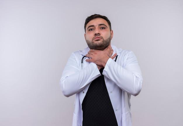 Jonge, bebaarde mannelijke arts die witte jas met een stethoscoop draagt die in paniek hand in hand om zijn hals verstikt