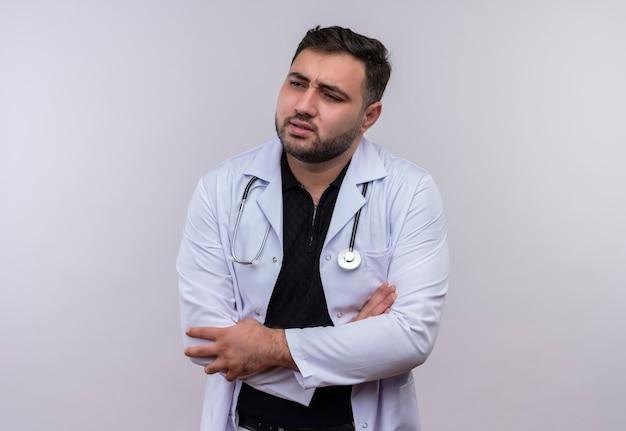 Jonge, bebaarde mannelijke arts die witte jas met een stethoscoop draagt die onwel kijkt wat betreft zijn buik