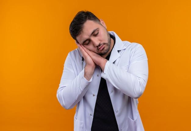 Jonge, bebaarde mannelijke arts die witte jas met een stethoscoop draagt die palmen tegen elkaar houdt leunend hoofd op palmen wil slapen