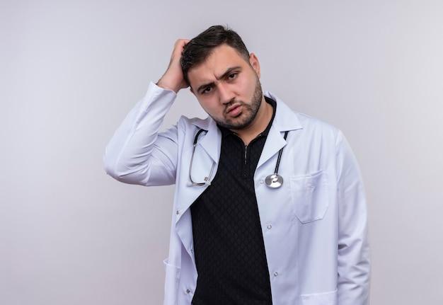 Jonge, bebaarde mannelijke arts die witte jas met een stethoscoop draagt die verward kijkt wat betreft hoofd met de hand