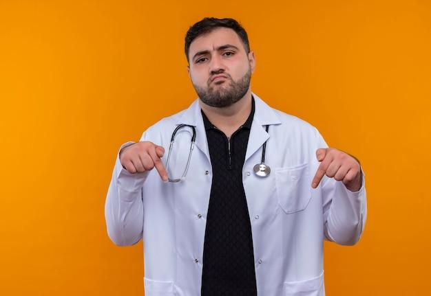 Jonge, bebaarde mannelijke arts die witte jas met een stethoscoop draagt die zelfverzekerd wijst wijsvingers naar beneden kijkt