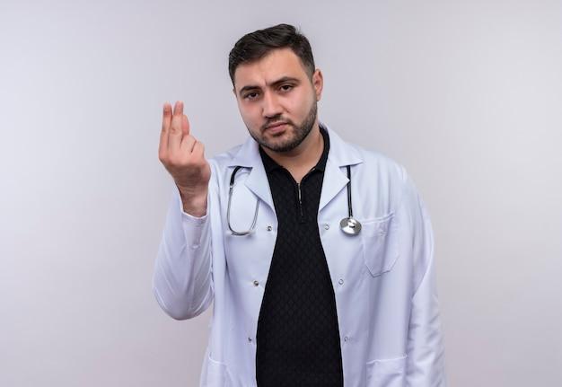 Jonge, bebaarde mannelijke arts die witte jas met stethoscoop draagt die camera bekijkt die het gebaar van het vingersgeld, vraagt om geld