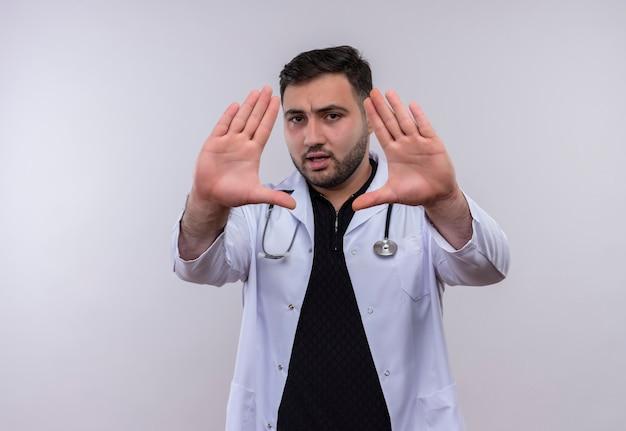 Jonge, bebaarde mannelijke arts die witte jas met stethoscoop draagt die met open handen stopteken met ernstig gezicht maakt