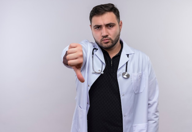 Jonge, bebaarde mannelijke arts die witte jas met stethoscoop draagt die ontevreden kijkt die afkeer toont
