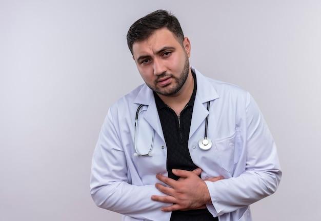 Jonge, bebaarde mannelijke arts die witte jas met stethoscoop draagt die onwel kijkt wat betreft zijn buik die pijn voelt