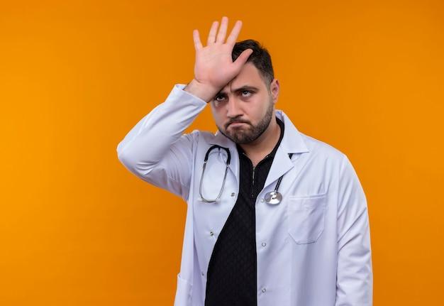 Jonge, bebaarde mannelijke arts die witte jas met stethoscoop met palm boven zijn hoofd draagt ?? die verward kijkt