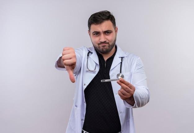 Jonge, bebaarde mannelijke arts die witte laag met de thermometer van de stethoscoopholding draagt die afkeer met ongelukkig gezicht toont