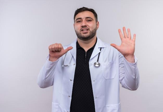 Jonge, bebaarde mannelijke arts die witte laag met stethoscoop draagt die en met vingers nummer zes benadrukt