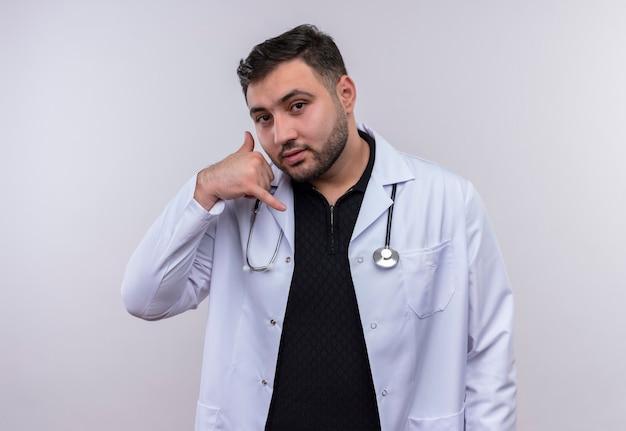 Jonge, bebaarde mannelijke arts die witte vacht met stethoscop draagt