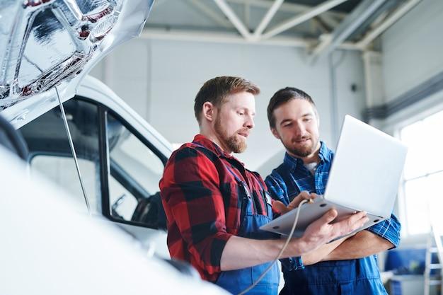 Jonge, bebaarde professionele technici of reparateurs met laptop die in het net surfen voor technische informatie