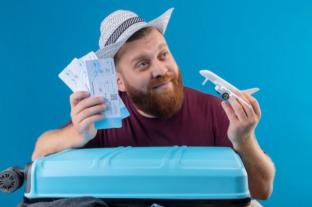 Jonge, bebaarde reiziger man in zomer hoed met koffer vol kleren met vliegtickets en speelgoed vliegtuig speels optimistisch en gelukkig lachend opzij kijken met dromerige blik over b