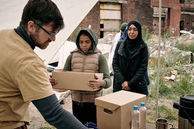 Jonge, bebaarde sociale medewerker in glazen die voedsel en water geeft aan zwart vluchtelingenmeisje met open doos buitenshuis
