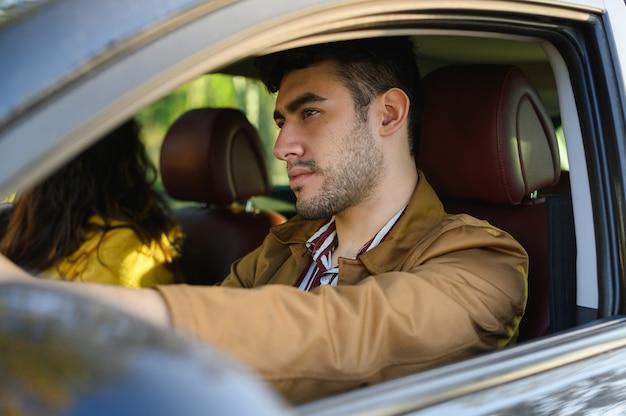 Jonge, bebaarde spaanse man die een auto bestuurt met zijn vriendin
