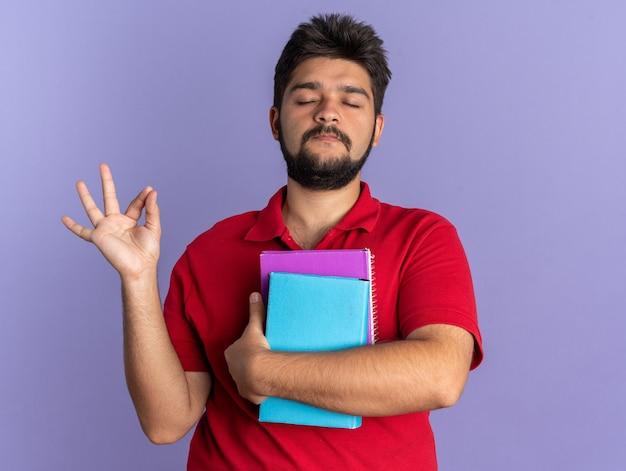 Jonge, bebaarde student in een rood poloshirt met boeken die een meditatiegebaar maakt, ontspannend met gesloten ogen over een blauwe muur