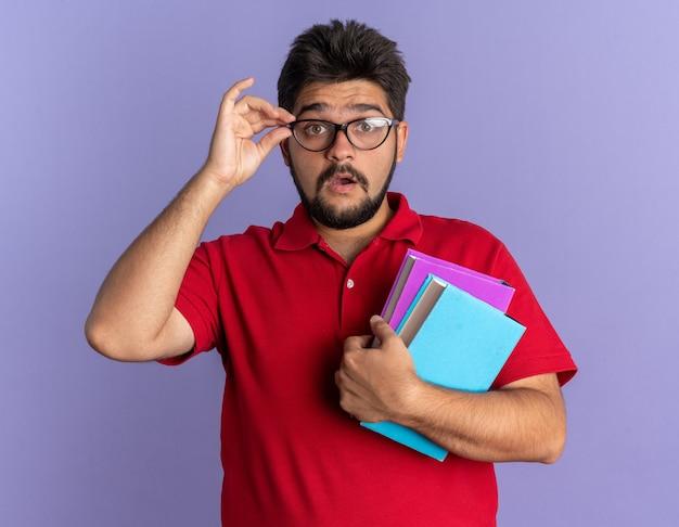 Jonge, bebaarde student in een rood poloshirt met een bril die boeken vasthoudt, verrast over de blauwe muur