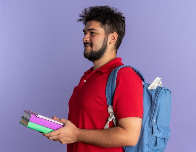 Jonge, bebaarde student in een rood poloshirt met een rugzak met boeken die opzij kijkt met een glimlach op een blij gezicht dat over een blauwe muur staat