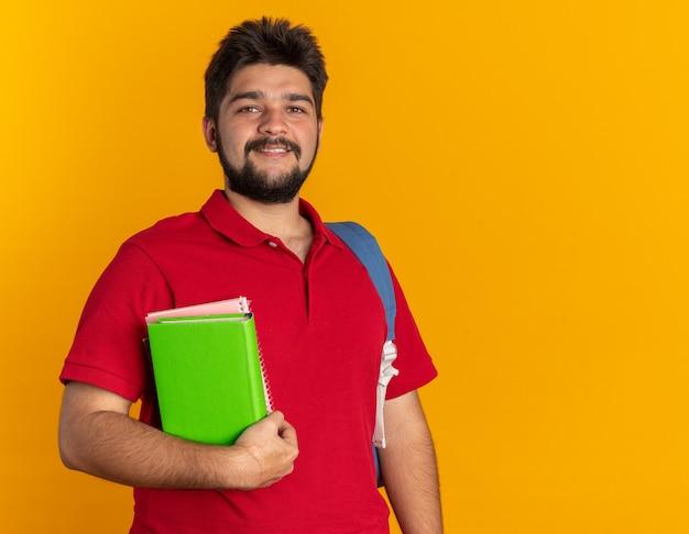 Jonge, bebaarde student in een rood poloshirt met een rugzak met boeken die vrolijk en zelfverzekerd lacht en over de oranje muur staat