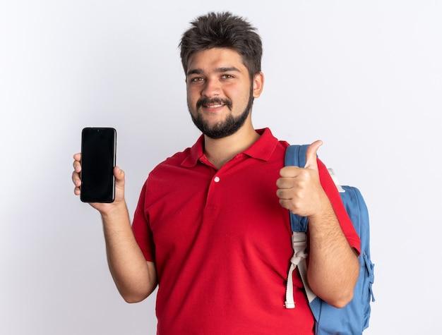Jonge, bebaarde student in een rood poloshirt met een rugzak met een smartphone die zelfverzekerd glimlacht en duimen opsteekt terwijl hij over een witte muur staat