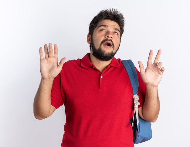 Jonge, bebaarde student in een rood poloshirt met rugzak die bezorgd opkijkt en over een witte muur staat
