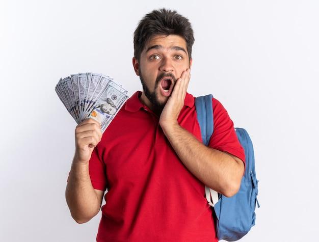 Jonge, bebaarde student in een rood poloshirt met rugzak die contant geld vasthoudt en er verbaasd en verrast uitziet
