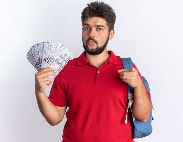 Jonge, bebaarde student in een rood poloshirt met rugzak die contant geld vasthoudt en er zelfverzekerd uitziet, wijzend met de wijsvinger staand