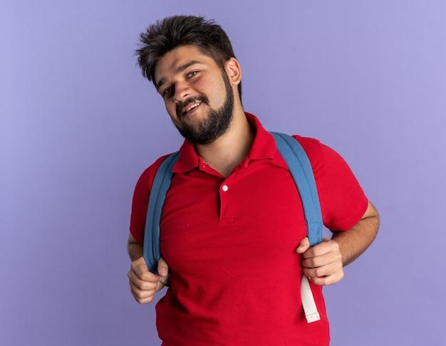 Jonge, bebaarde student in een rood poloshirt met rugzak die er glimlachend zelfverzekerd, gelukkig en positief uitziet