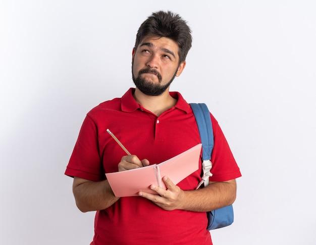 Jonge, bebaarde student in een rood poloshirt met rugzak die in een notitieboekje schrijft en verbaasd opkijkt terwijl hij over een witte muur staat