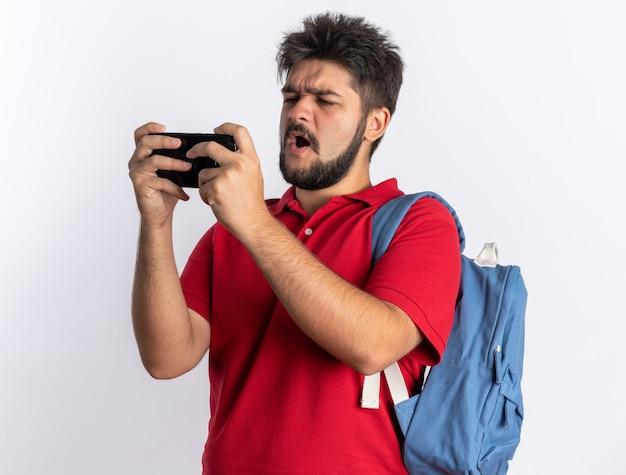 Jonge, bebaarde student in een rood poloshirt met rugzak die spelletjes speelt met een smartphone die er blij en opgewonden uitziet