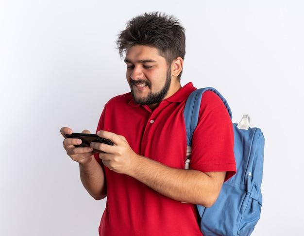 Jonge, bebaarde student in een rood poloshirt met rugzak die spelletjes speelt met smartphone gelukkig en vrolijk staand