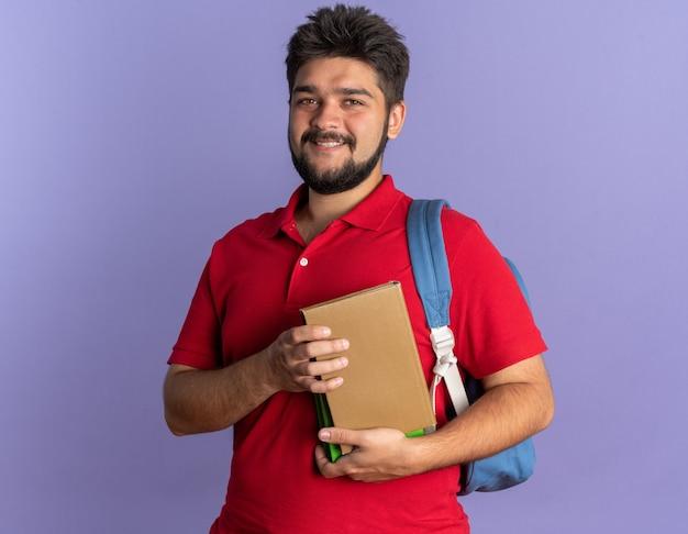 Jonge, bebaarde student in een rood poloshirt met rugzak met boeken die er vrolijk en positief uitziet
