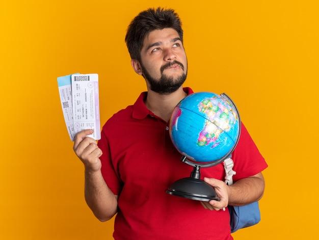 Jonge, bebaarde student in een rood poloshirt met rugzak met globe en vliegtickets, geïntrigeerd en gelukkig opkijkend