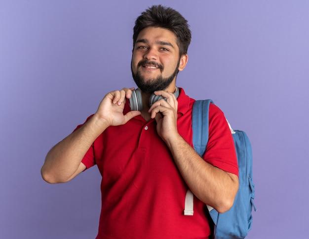 Jonge, bebaarde student in een rood poloshirt met rugzak met koptelefoon die er vrolijk vrolijk en positief uitziet