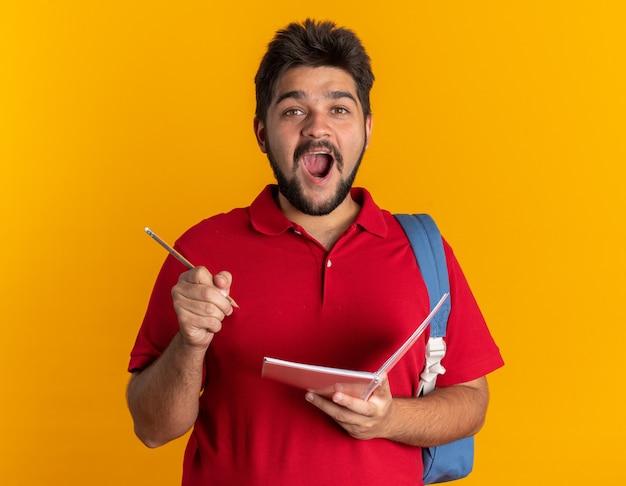 Jonge, bebaarde student in een rood poloshirt met rugzak met notitieboekje en potlood verbaasd en verrast met een nieuw idee dat over de oranje muur staat