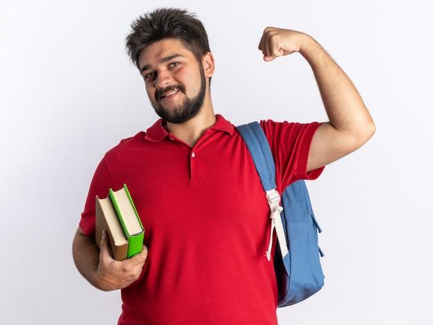 Jonge, bebaarde student in een rood poloshirt met rugzak met notitieboekjes, blij en positief uitziende vuist glimlachend staand