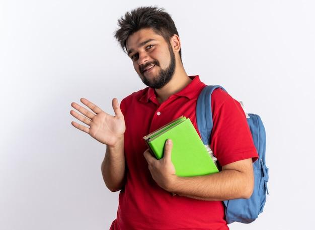 Jonge, bebaarde student in een rood poloshirt met rugzak met notitieboekjes, blij en vrolijk glimlachend zwaaiend met de hand over een witte muur