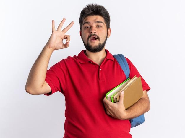 Jonge, bebaarde student in een rood poloshirt met rugzak met notitieboekjes die er blij en positief uitziet met een ok teken dat over een witte muur staat