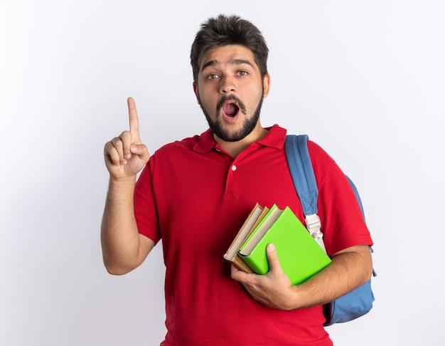Jonge, bebaarde student in een rood poloshirt met rugzak met notitieboekjes die er blij en verrast uitziet met een wijsvinger nieuw idee concept staand