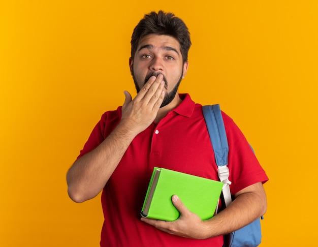 Jonge, bebaarde student in een rood poloshirt met rugzak met notitieboekjes die er geschokt uitziet en zijn mond bedekt met de hand staand