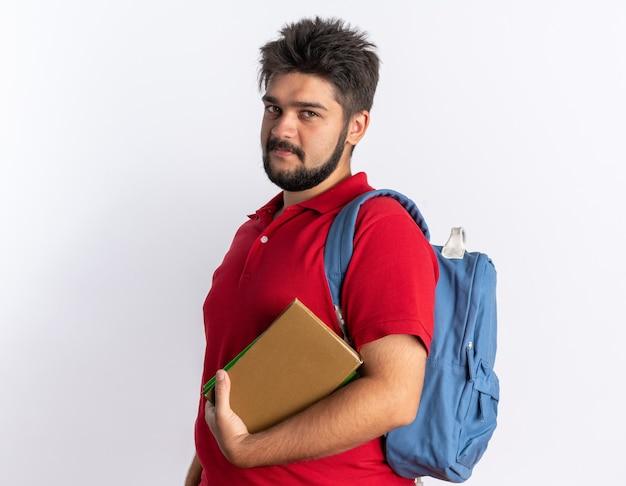 Jonge, bebaarde student in een rood poloshirt met rugzak met notitieboekjes die er glimlachend gelukkig en positief uitziet