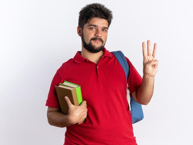 Jonge, bebaarde student in een rood poloshirt met rugzak met notitieboekjes die er glimlachend uitziet en nummer drie toont met vingers gelukkig en positief staand
