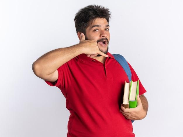 Jonge, bebaarde student in een rood poloshirt met rugzak met notitieboekjes die er glimlachend vrolijk uitziet en me een gebaar maakt staand