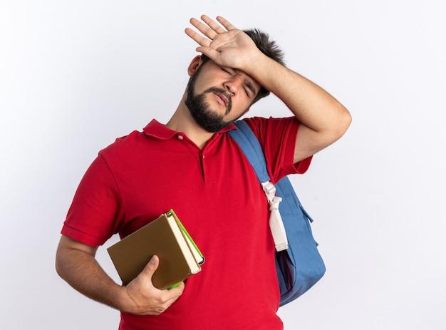 Jonge, bebaarde student in een rood poloshirt met rugzak met notitieboekjes die er moe en overwerkt uitziet en over een witte muur staat
